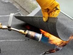 Installation of roofing material using a torch